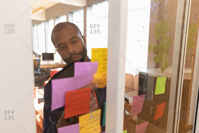 Front view close up of a young African American man writing notes on a glass wall during a team brainstorm session at a creative office, seen through glass wall
