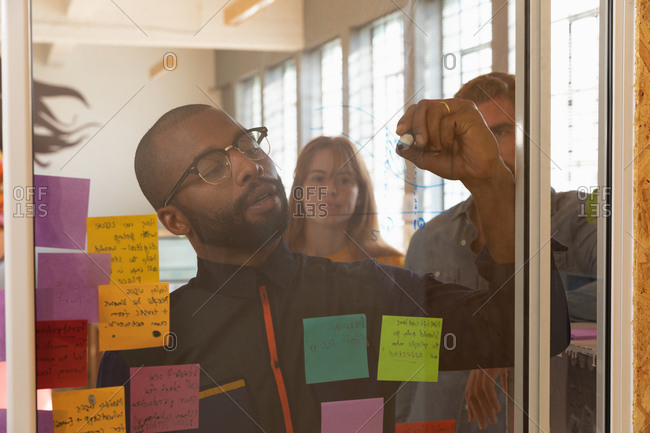 Front view close up of a young African American man wearing glasses writing notes on a glass wall during a team brainstorm session at a creative office, seen through glass wall with colleagues standing behind him watching