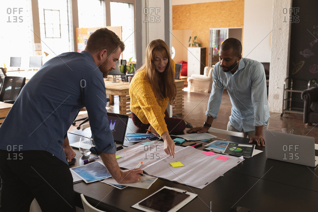 Side view of a young African American man and a young Caucasian man and woman standing and leaning over a desk working together on a project in a creative office