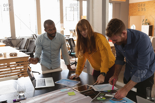 Front view close up of a young African American man and a young Caucasian man and woman standing and leaning over a desk working together on a project in a creative office