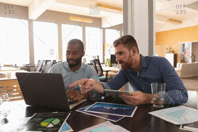 Front view close up of a young African American man and a young Caucasian man sitting at a desk using a laptop computer looking at visuals and talking together in a creative office