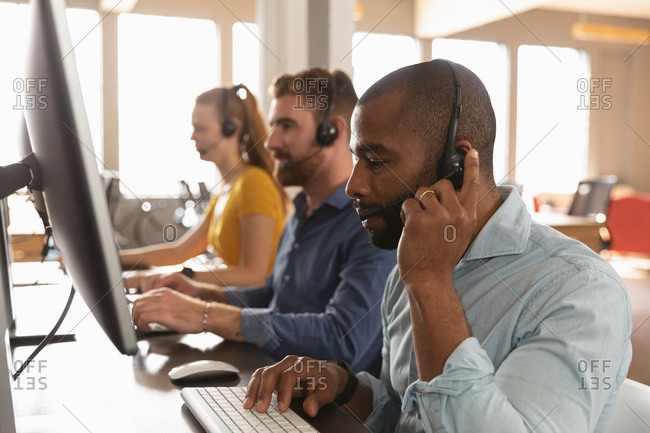 Side view close up of a young African American man and a young Caucasian woman and man sitting at desks using computers and talking on phone headsets in a creative office