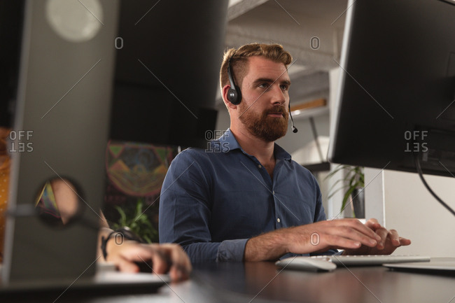 Front view close up of a young Caucasian man sitting at a desk using a computer and wearing a phone headset in a creative office, seen between computer screens, with the hand of a colleague working beside him on the desk