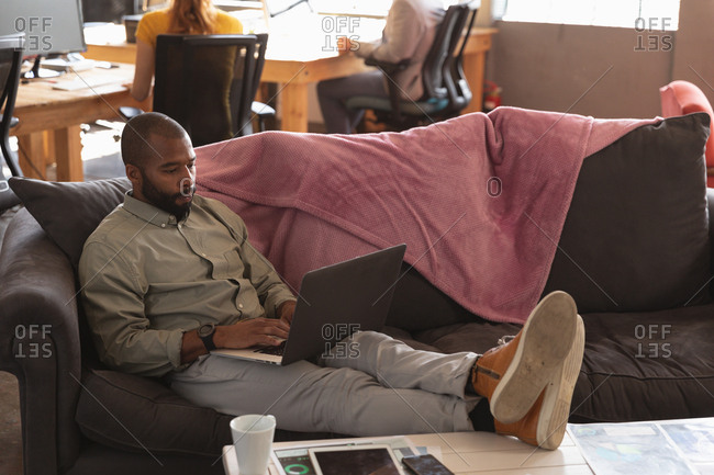 Front view close up of a young African American man sitting on a sofa with his feet up on a table using a laptop computer in the lounge area of a creative office, with a colleague working in the background