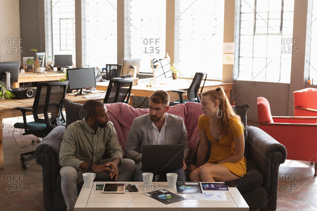 Front view of a young African American man and a young Caucasian woman and man sitting on a sofa in a creative office discussing a project and using a laptop computer