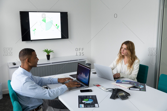 Side view of a young African American man and a young Caucasian woman sitting at opposite sides of a desk talking and using laptop computers in the modern office of a creative business