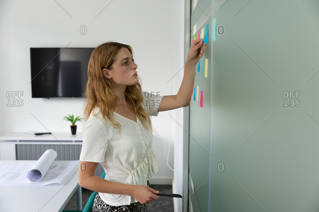Side view close up of a young Caucasian woman standing and sticking colored sticky notes on a glass wall in the modern office of a creative business
