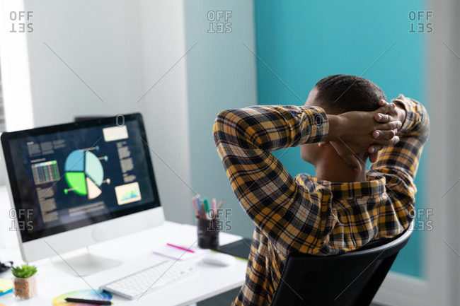 Rear view close up of a young African American man sitting at a desk with his hands behind his head looking at a computer monitor in the modern office of a creative business