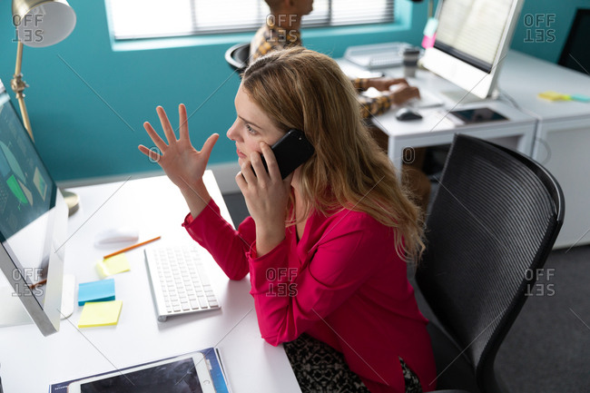 Side view close up a young Caucasian woman sitting at a desk in front of a computer talking on a smartphone and gesturing with her hand raised, in the modern office of a creative business, with her male colleague sitting and working at a computer in the background