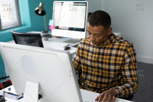 Front view of a young African American man sitting at a desk using a computer in the modern office of a creative business, with an empty workstation in the background