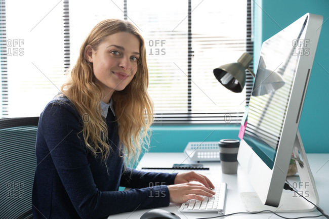 Side view close up of a young Caucasian woman sitting at a desk by a window using a computer, turning and smiling to camera in the modern office of a creative business