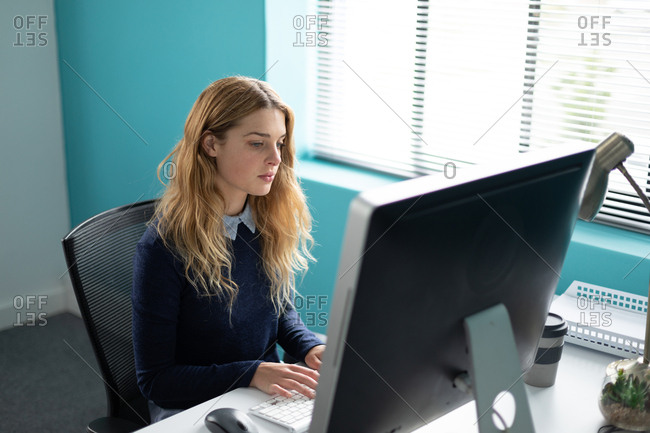 Side view of a young Caucasian woman sitting at a desk by a window using a computer, turning and smiling to camera in the modern office of a creative business