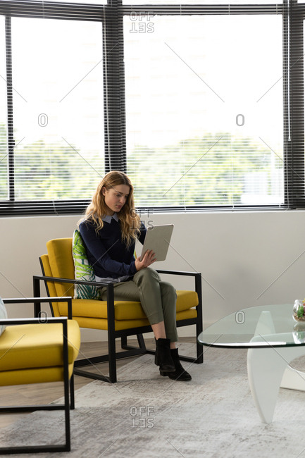 Front view of a young Caucasian woman sitting in an armchair using a tablet computer in front of a window in the lounge area of a creative business