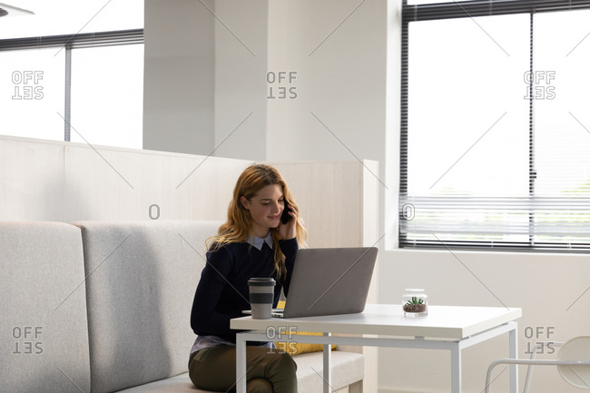 Front view of a young Caucasian woman sitting on a bench seat using a laptop computer and talking on a smartphone at a table with a cup of coffee in the dining area of a creative business