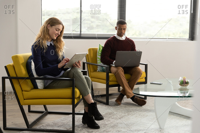 Side view of a young Caucasian woman using a tablet computer and a young African American man using a laptop computer sitting in armchairs in the lounge area of a creative business