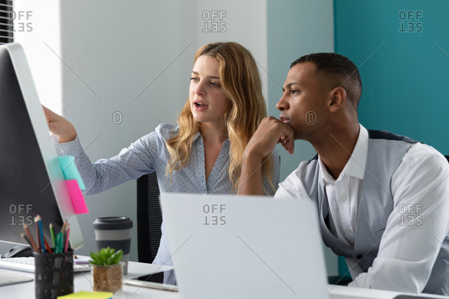 Side view close up of a young African American man using a laptop computer listening to a young Caucasian woman talking and pointing to a computer monitor, sitting together at a desk in the modern office of a creative business
