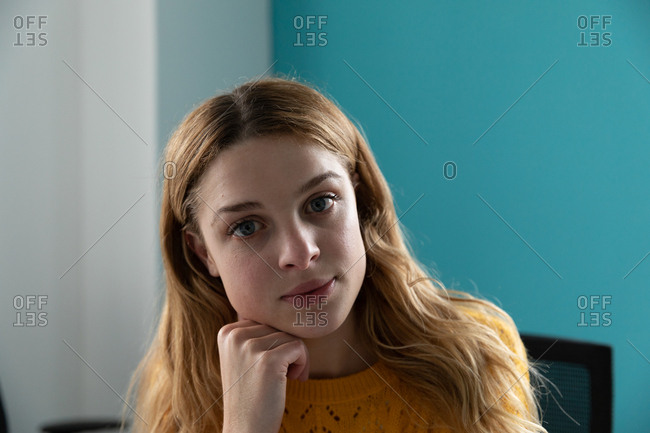 Portrait close up of a young Caucasian woman with long blonde hair and blue eyes resting her chin on her hand, looking straight to camera in the office of a creative business