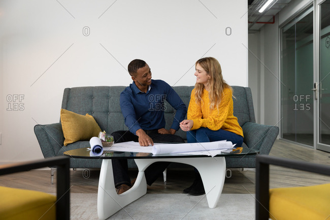 Front view of a young African American man and a young Caucasian woman talking and looking at plans together sitting on a sofa in the lounge area of a modern creative business
