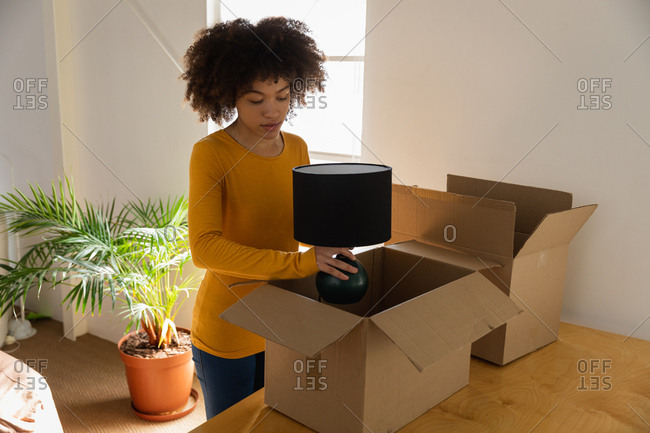 Front view of a young mixed race woman unpacking boxes at a creative office