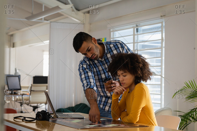Side view of a young mixed race man standing and a young mixed race woman sitting at a desk having a discussion at a creative office