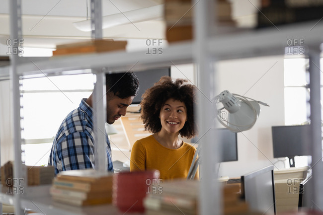 Side view of a young mixed race man and a young mixed race woman sitting at a desk having a discussion at a creative office