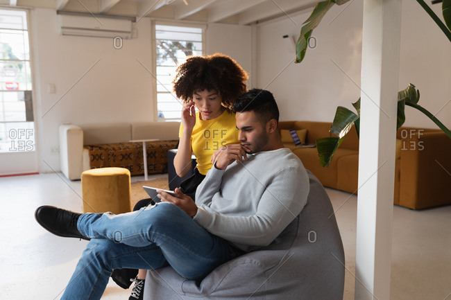 Front view of a young mixed race man and a young mixed race woman sitting on a bean bag using a tablet computer and having a discussion at a creative office