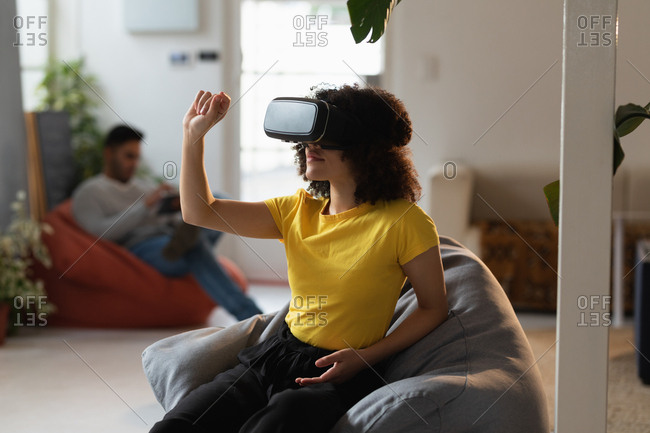 Front view of a young mixed race woman using a VR headset and a young mixed race man sitting in the background at a creative office