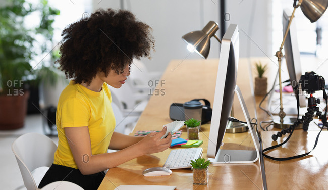 Side view of a young mixed race woman sitting at a desk looking at color swatches at a creative office