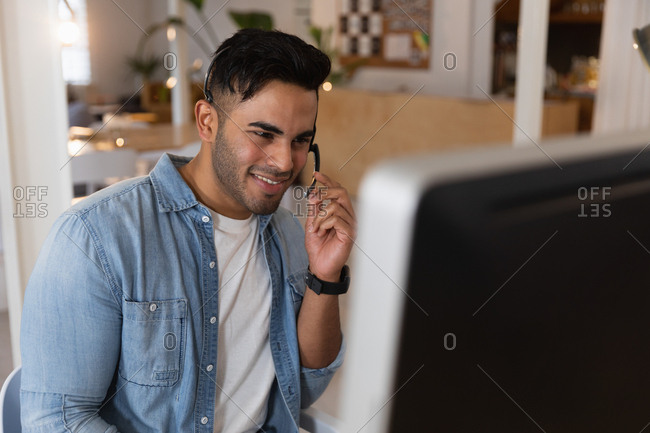 Front view close up of a young mixed race man sitting at a desk wearing a headset and looking at a computer screen at a creative office