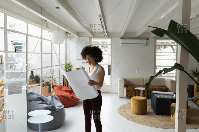 Front view of a young mixed race woman standing and checking an architectural drawing at a creative office