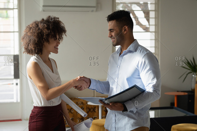 Side view close up of a young mixed race man and a young mixed race woman standing and shaking hands at a creative office