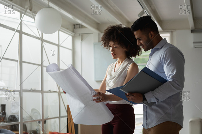 Side view close up of a young mixed race man and a young mixed race woman standing and checking an architectural drawing at a creative office