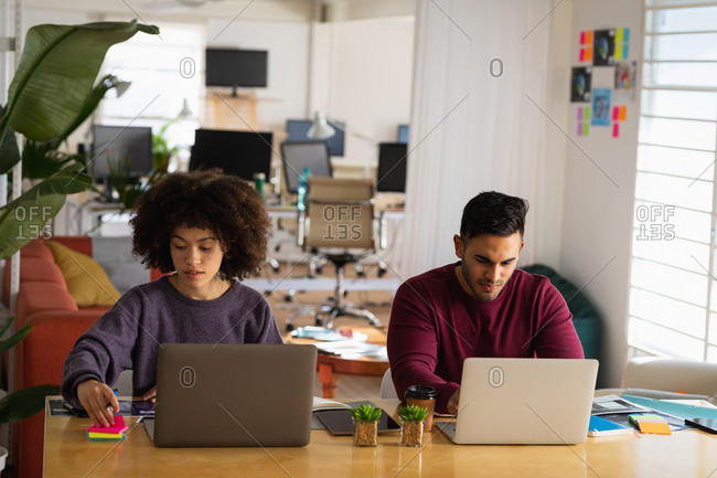 Front view of a young mixed race man and a young mixed race woman sitting at a desk using laptop computers at a creative office