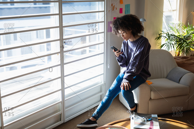 Side view of a young mixed race woman sitting on an armchair and using a smartphone at a creative office