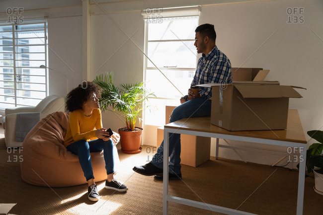 Side view close up of a young mixed race man sitting on a desk and a young mixed race woman sitting on a bean bag having a discussion with cardboard boxes at a creative office