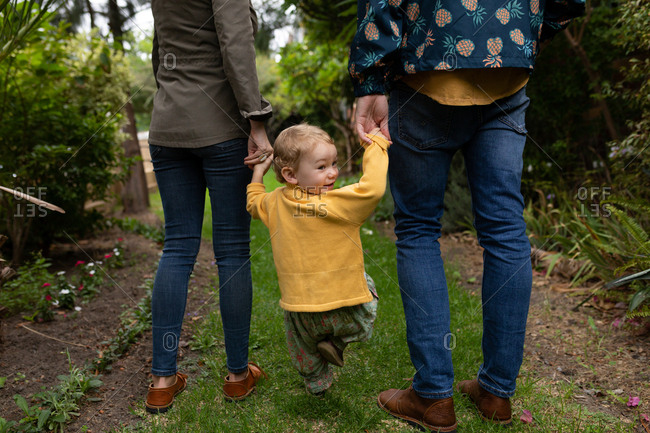 Rear view of a low section of a young Caucasian father and mother  holding hands with their baby and walking in a garden, baby is turning around