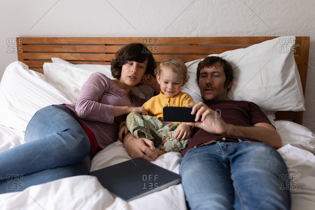 Front view of a young Caucasian father and mother lying on a bed and using a smartphone with their baby
