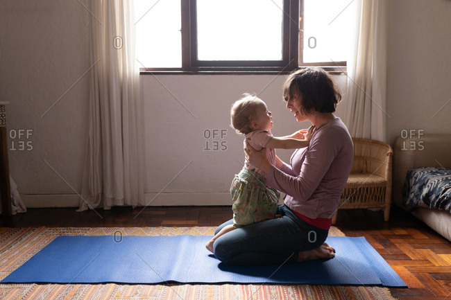 Side view of a young Caucasian mother sitting on a floor and holding her baby, looking at each other
