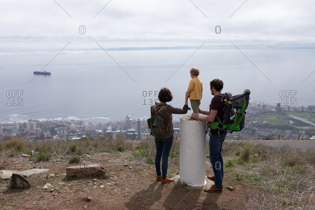 Rear view of a young Caucasian father and mother standing in a park with their baby between them and enjoying the view