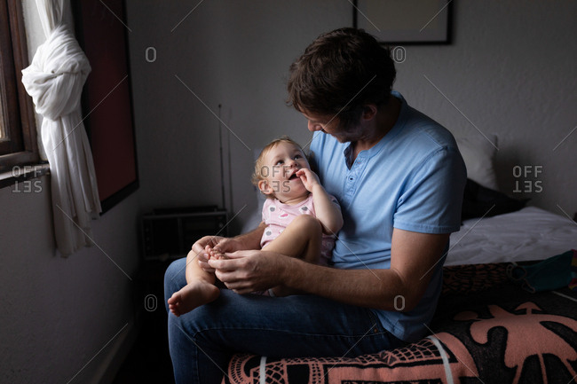 Front view of a young Caucasian father holding his baby, sitting on a bed and looking at each other