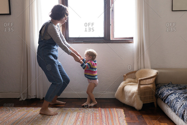 Side view of a young Caucasian mother dancing with her baby, looking at each other
