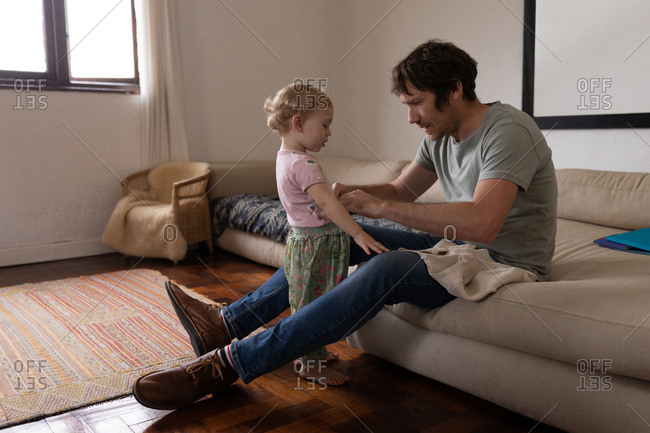 Side view of a young Caucasian father getting his baby dressed, sitting on a couch