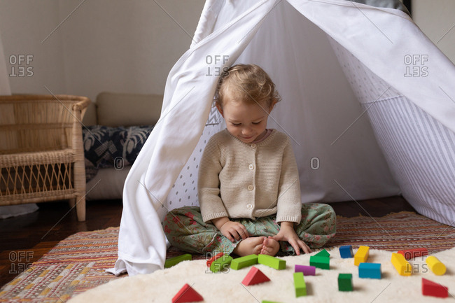 Front view of a Caucasian baby sitting on a floor and playing with wooden blocks, barefoot