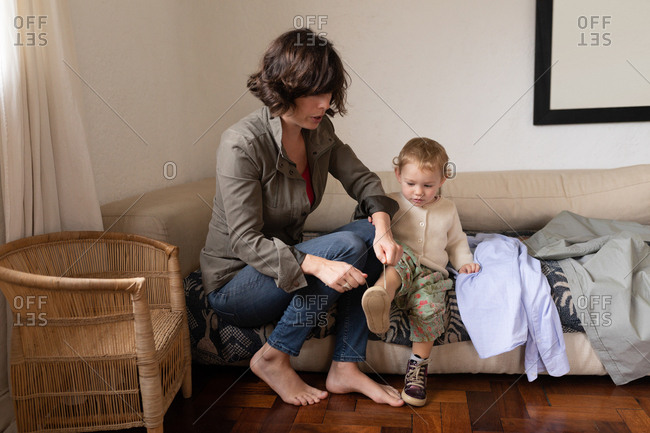Front view of a young Caucasian mother getting her baby dressed, sitting on a couch
