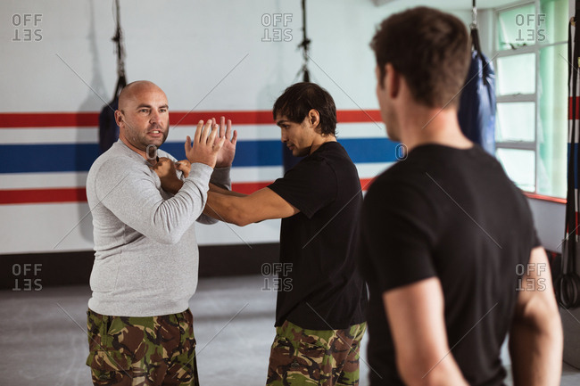Side view close up of a middle aged Caucasian male instructor giving self defense training in a boxing gym demonstrating a hold on a young mixed race man, while another young man looks on