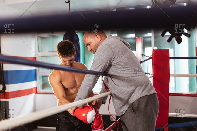 Side view close up of a young Caucasian male boxer by a boxing ring having his boxing gloves checked by a middle aged Caucasian male trainer