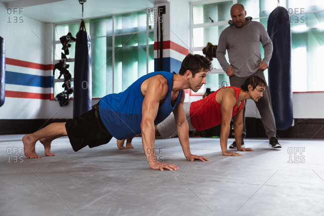 Side view of a young mixed race and a young Caucasian male boxers doing push ups while a middle aged Caucasian male trainer is standing next to them in a boxing gym