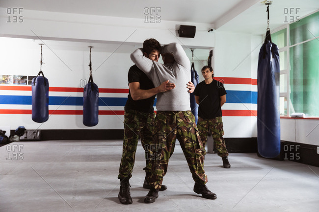 Front view of a middle aged Caucasian male instructor giving self defense training in a boxing gym demonstrating a hold on a young mixed race man, while another young man looks on