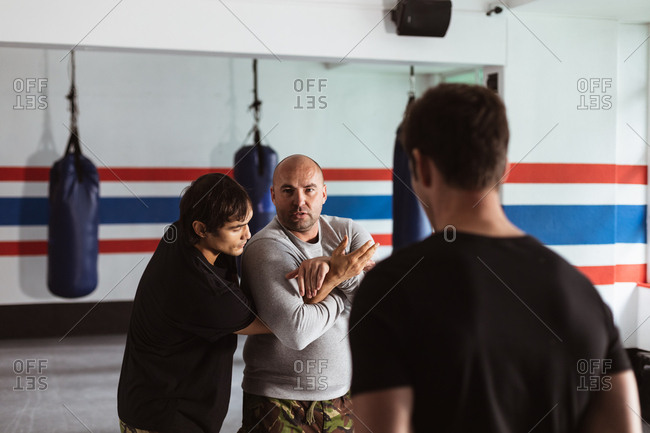 Front view close up of a middle aged Caucasian male instructor giving self defense training in a boxing gym demonstrating a hold on a young mixed race man, while another young man looks on