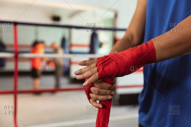 Side view mid section of a young mixed race male boxer in a boxing ring wrapping his hands while another young man is boxing in a background